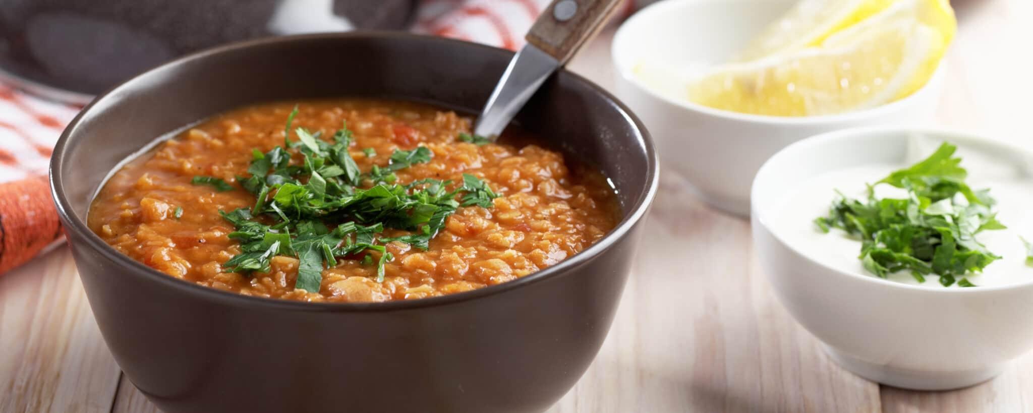 Soupe de lentille surmontée de coriandre dans un bol gris foncé, et accompagnée d'un ramequin de yaourt grec et d'un ramequin de quarts de citron